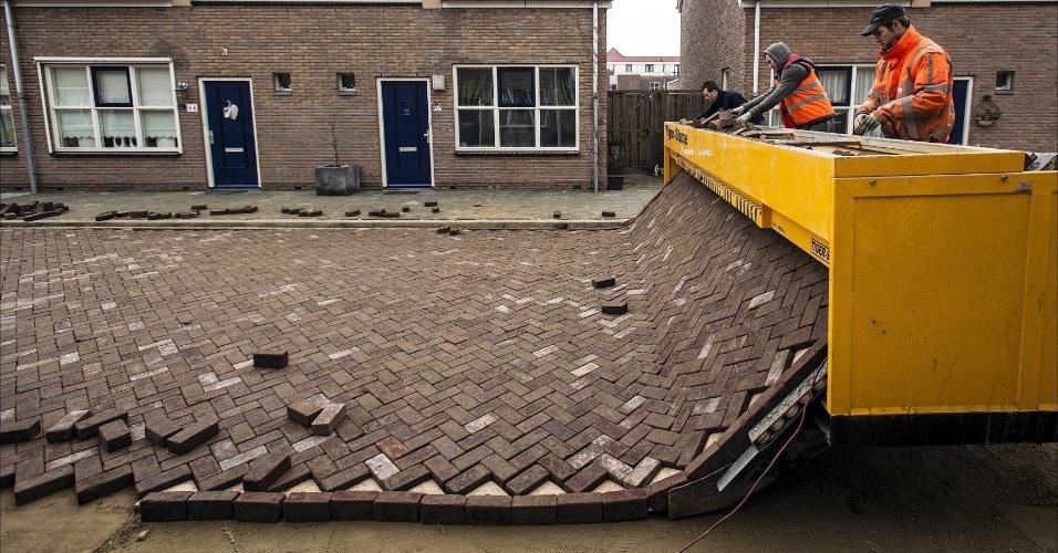 19.fev.2013 - Operários usam uma máquina especial para pavimentar uma rua em Ijmuiden, na Holanda