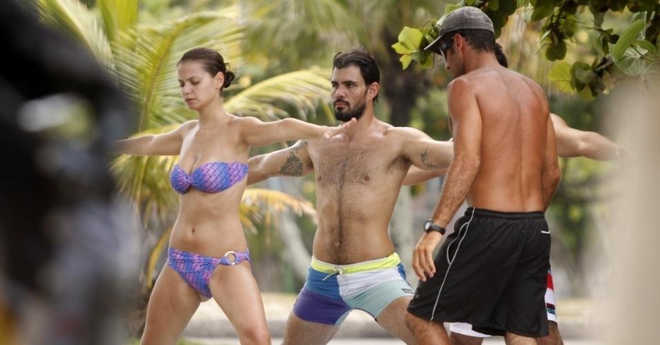 19.fev.2013 - Os atores Milena Toscano e Juliano Cazarré recebem instrução de professores durante aula de stand-up paddle na praia da Barra da Tijuca