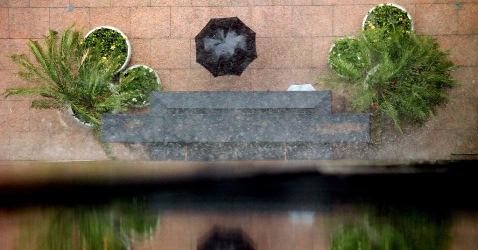19.fev.2013 - Uma pessoa usa o guarda-chuva ao sair de um dos prédios da avenida Faria Lima, zona oeste de São Paulo, durante a forte chuva que atingiu diversas regiões da cidade nesta terça-feira (19)