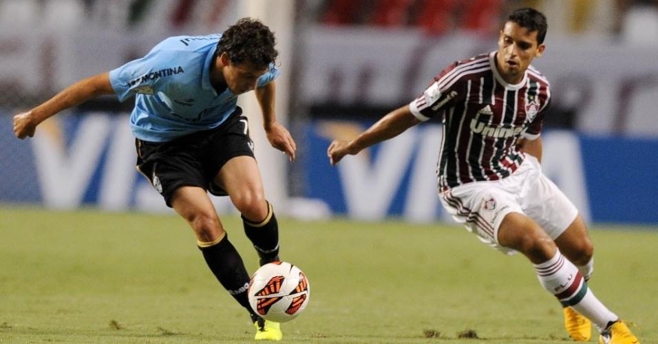 20.fev.2013 - Elano, meia do Grêmio, tenta lançamento observado pelo volante Jean, do Fluminense