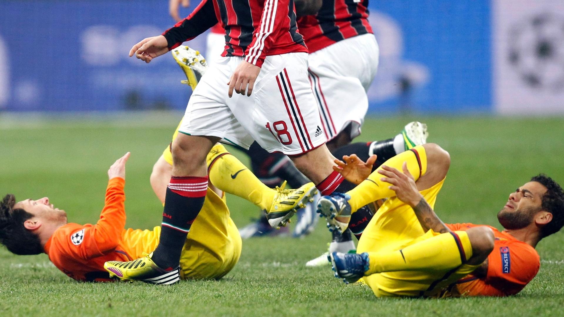 20.fev.2013 - Montolivo, do Milan, passa por Messi (esq.) e Daniel Alves (dir), caídos no gramado