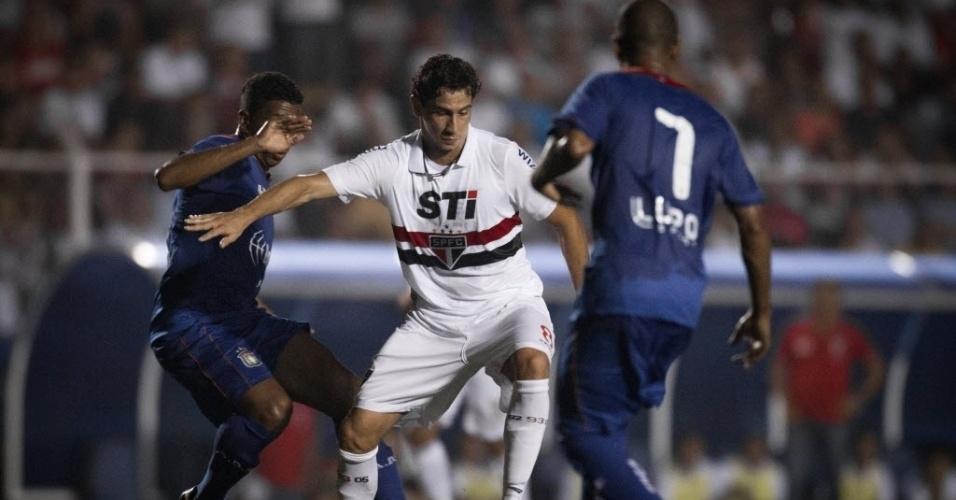 20.fev.2013 - Paulo Henrique Ganso tenta se livrar da marcação de jogador do São Caetano durante partida no ABC