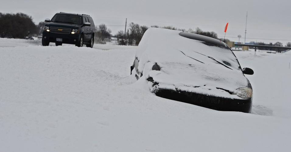 21.fev.2013 - Carro é parcialmente enterrado pela neve em Wichita, no Kansas (Estados Unidos), nesta quinta-feira (21). Uma frente de neve passa pela região central dos Estados Unidos
