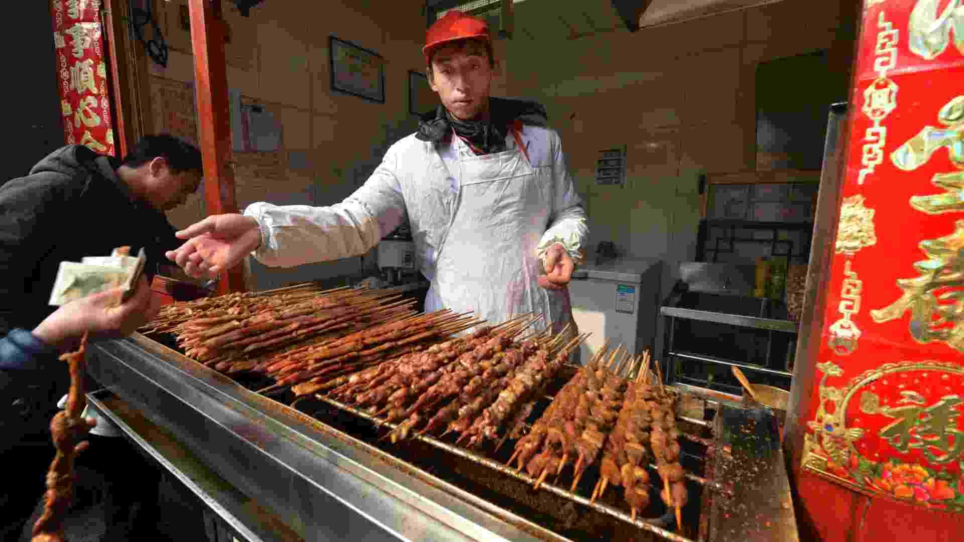 21.fev.2013 - Homem vende churrasco de carneiro em rua comercial de Pequim, na China. O governo do país cogita a possibilidade de banir essa atividade em centros urbanos para reduzir a poluição do ar - Mark Ralston/AFP