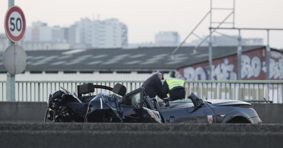 21.fev.2013 - Investigadores observam carro da polícia que ficou totalmente destruído depois de perseguição a criminosos que resultou na morte de dois policiais mortos em Porte de la Chapelle, em Paris (França)
