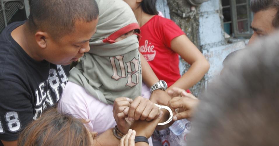 21.fev.2013 - O filipino Jerry de Leon se entrega a polícia após ter mantido sua ex-namorada como refém por seis horas em Manila