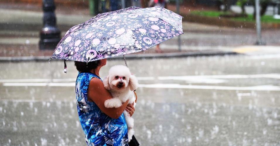22.fev.2013 - Mulher se protege da chuva forte da tarde desta sexta-feira (22), na avenida São João, centro de São Paulo. Por volta das 15h, quase toda a cidade, com exceção da zona sul, estava em estado de atenção para alagamentos, segundo CGE (Centro de Gerenciamento de Emergências)
