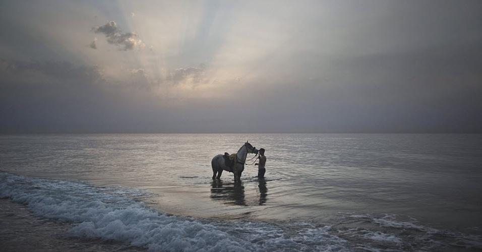22.fev.2013 - Palestino lava seu cavalo em praia na Faixa de Gaza, ao pôr do sol