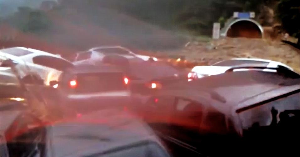 22.fev.2013 - Carros se amontoam na entrada de túnel, na rodovia dos Imigrantes, que liga a baixada santista a São Paulo, após um deslizamento de terra e rochas, causado pela enxurrada em um rio que passa abaixo, e a tempestade que caiu nesta sexta