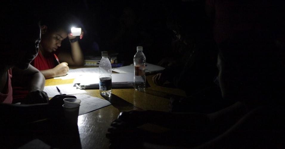 23.fev.2013 - Cadastro de pessoas que perderam suas casas em Cubatão, no litoral de São Paulo, é feito com ajuda da luz de celulares depois que o Centro Esportivo Humberto de Alencar ficou sem luz