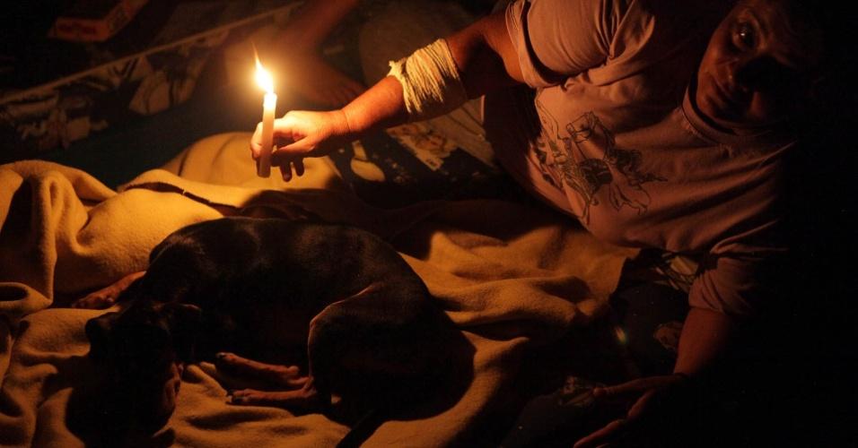 23.fev.2013 - Desalojados da chuva de Cubatão, no litoral de São Paulo, usam velas no Centro Esportivo Humberto de Alencar, após a queda de energia no abrigo