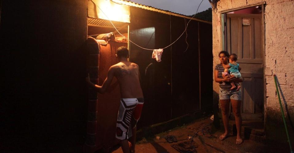 23.fev.2013 - Família retira móveis de casa neste sábado (23), após enxurrada atingir Cubatão, no litoral de São Paulo