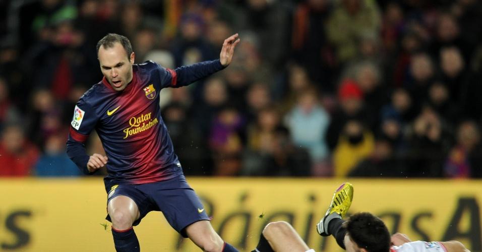 23.fev.2013 - Iniesta (de pé), do Barcelona, se livra de marcador do Sevilla