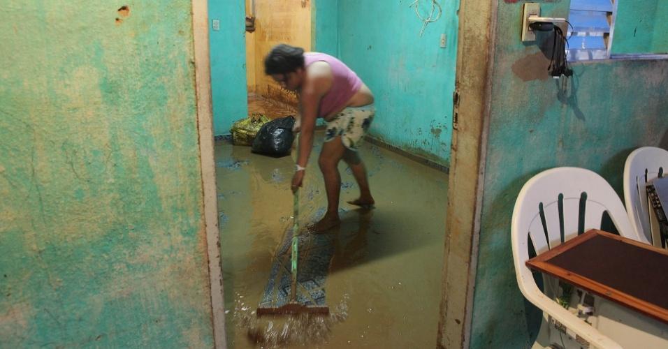 23.fev.2013 - Mulher retira lama de casa após o bairro de Água Fria, em Cubatão, cidade no litoral de São Paulo, ter ficado alagado com temporal