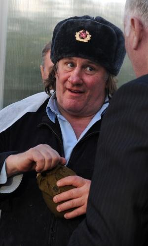23.fev.2013 - O ator Gerard Depardieu, que ganhou cidadania russa em janeiro passado, usa chapéu militar russo em visita à fazenda Teplichnoye, no vilarejo de Ozerny, na Rússia, neste sábado (23)