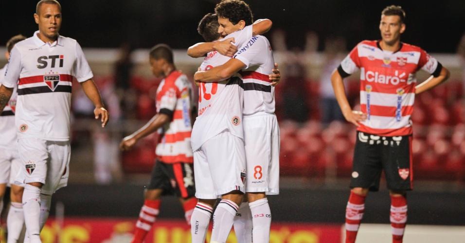 23.fev.2013 Paulo Henrique Ganso e Jadson se abraçam após gol marcado pelo São Paulo na partida contra o Linense, neste sábado