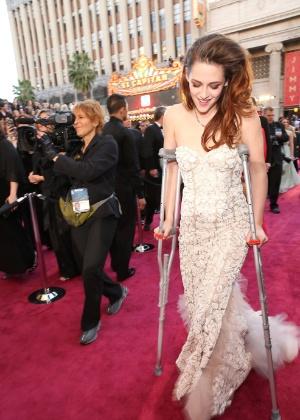 """Com a ajuda de uma muleta, a atriz de """"Crepúsculo"""", Kristen Stewart, chega ao tapete vermelho do Oscar 2013 - Getty Images"""