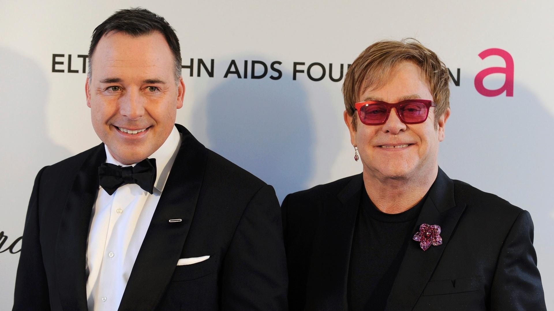 24.fev.2013 - O cantor Elton John e o parceiro David Furnish comparecem a festa que promovem antes da premiação para arrecadar fundos para combater a AIDS