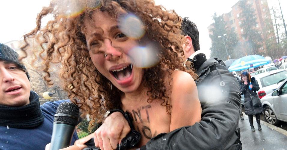 24.fev.2013 - Feministas do grupo Femen protestam contra ex-primeiro ministro italiano Silvio Berlusconi, do lado fora de onde o político está votando, na Itália. A população vai às urnas neste domingo e segunda-feira (25) nas eleições gerais no país