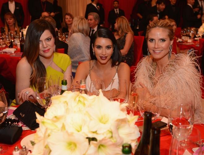 24.fev.2013 - As irmãs Kardashian, Kloe e Kim, se juntam a Heidi Klum na mesa da festa beneficente promovida por Elton John