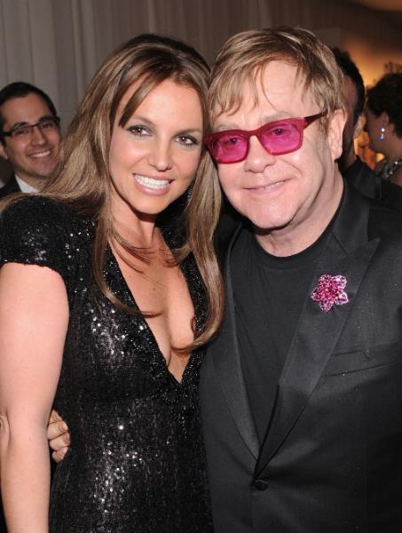 24.fev.2013 - De cabelos mais escuros, Britney Spears posa ao lado de Elton John na festa beneficente em prol do combate à Aids, promovida pelo cantor após a cerimônia do Oscar