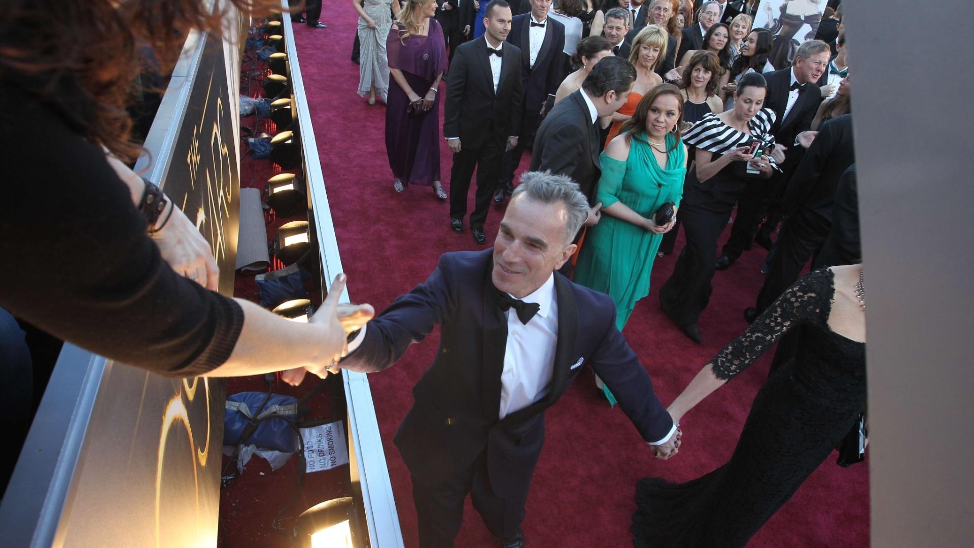 24.fev.2013 - Favorito para ganhar seu terceiro Oscar, Daniel Day-Lewis cumprimenta fã no tapete vermelho