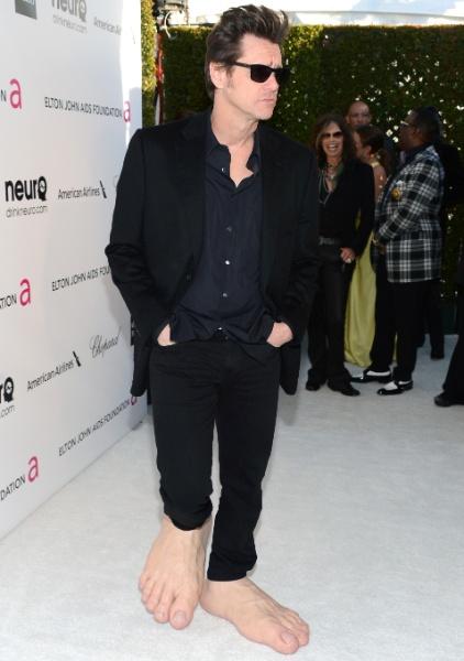 """24.fev.2013 - Jim Carrey faz graça na festa de Elton John e aparece com pés gigantes. No fundo, Steven Tyler acha graça do """"figurino"""" do ator"""