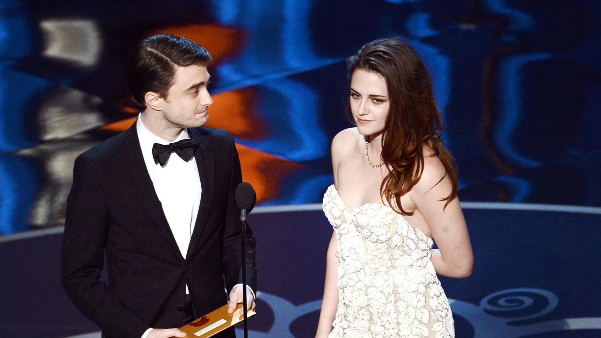 24.fev.2013 - Kristen Stewart entra mancando no palco, acompanhada de Daniel Radcliffe, para anunciar o vencedor de Melhor Direção de Arte