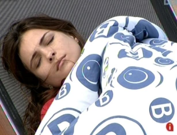 25.fev.2013 - Após comer brigadeiro e sentindo frio, Kamilla busca cobertor e deita numa espreguiçadeira do lado de fora da casa