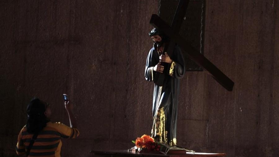 25.fev.2013 - Mulher tira foto com seu celular de estátua de Jesus Cristo na catedral de Manágua (Nicarágua) - Oswaldo Rivas/Reuters