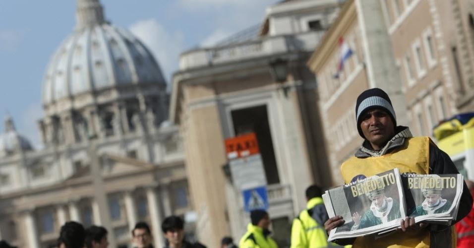 24.fev.2013 - Homem vende jornal em Roma com foto de Bento 16 na capa e matéria sobre a renúncia do papa