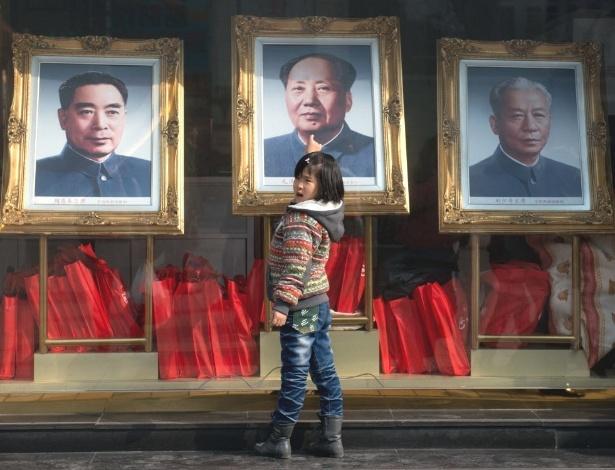 Criança observa retratos de ex-líderes chineses (da esquerda para a direita, Zhou Enlai, Mao Zedong e Liu Shaoqi)