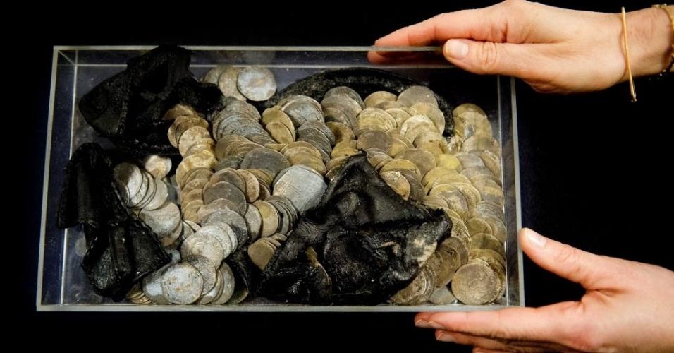 """26.fev.2013 - Um trabalho de escavação arqueológica encontrou 477 moedas de prata dentro de um sapato enterrado na Prefeitura de Roterdã, na Holanda - estima-se que o tesouro possa valer """"alguns milhares de euros"""". Os arqueólogos suspeitam que o dono do sapato escondeu as moedas para proteger sua fortuna durante a Guerra dos Oitenta Anos, que ocorreu entre 1568 e 1648"""
