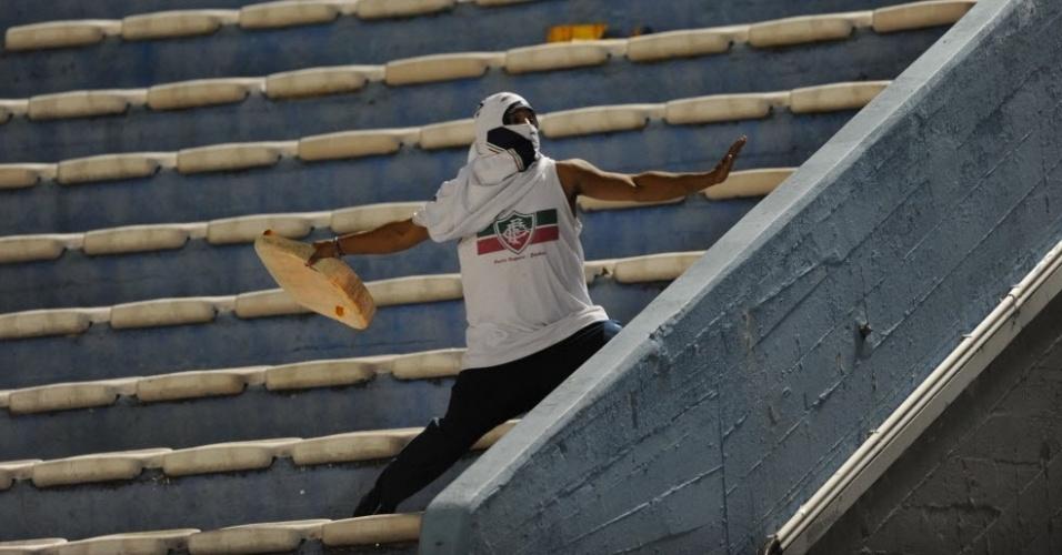 O jogo entre Peñarol e Vélez Sarsfield teve episódios de violência. As duas torcidas brigaram e jogaram objetos e pedras umas nas outras, obrigando a polícia a reforçar a segurança no local e aumentar o espaço entre as duas torcidas. Na foto, um homem vestido com uma camisa com escudo do Fluminense arremessa uma pedra contra os fãs adversários.