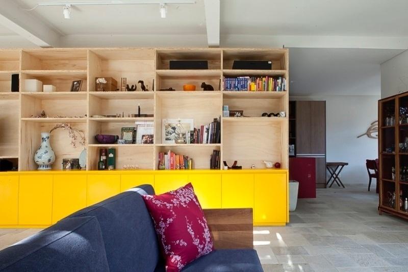 Os arquitetos Tito e Chantal Ficarelli, do escritório Arkitito, optaram por aplicar a tonalidade amarela vibrante somente na parte inferior da estante. Outras cores compõem o ambiente de estar: o azul do sofá e o tom rosa da almofada