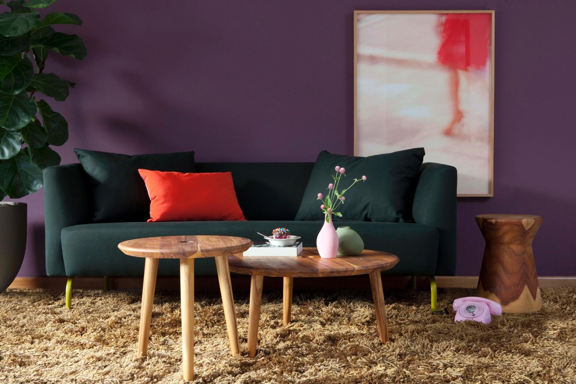 Para a decoração da sala, a arquiteta Yáskara  Idemori combinou a parede na cor Luxúria - R225 (Tinta Suvinil) com o sofá Flipper, assinado pelo designer Fernando Jaeger, revestido com tecido lona no tom verde escuro