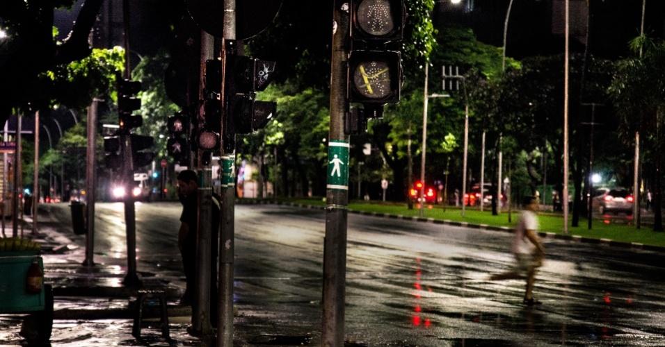 26.fev.2013 - Pedestre atravessa correndo a avenida Brigadeiro Faria Lima, no cruzamento com a avenida Rebouças, na zona oeste de São Paulo, onde todos os semáforos estavam apagados nesta noite, em consequência da chuva que atingiu a cidade no fim de tarde