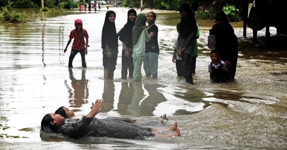 27.fev.2013 - Crianças brincam em água de enchente na cidade de Narathiwat, no sul da Tailândia, nesta quarta-feira (27)