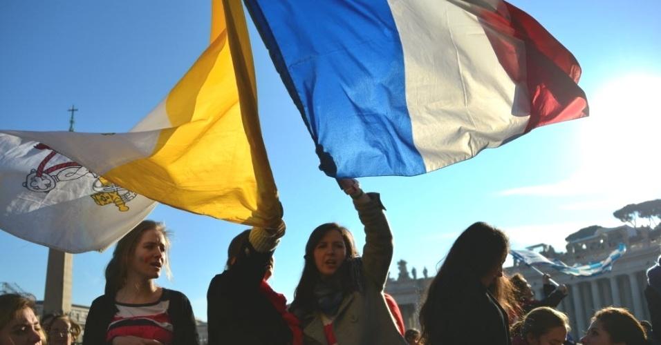 27.fev.2013 - Fiéis agitam bandeiras na praça São Pedro, no Vaticano, às vésperas do último sermão do papa Bento 16. O líder da Igreja Católica renunciará oficialmente ao cargo na quinta-feira (28)