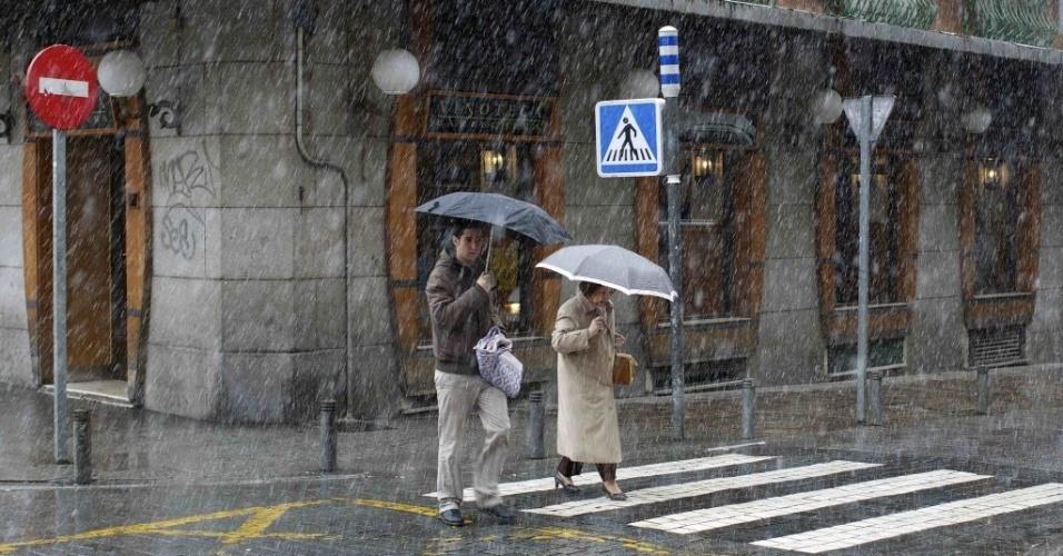 27.fev.2013 - Pedestres se protegem de nevasca em Madri, na Espanha