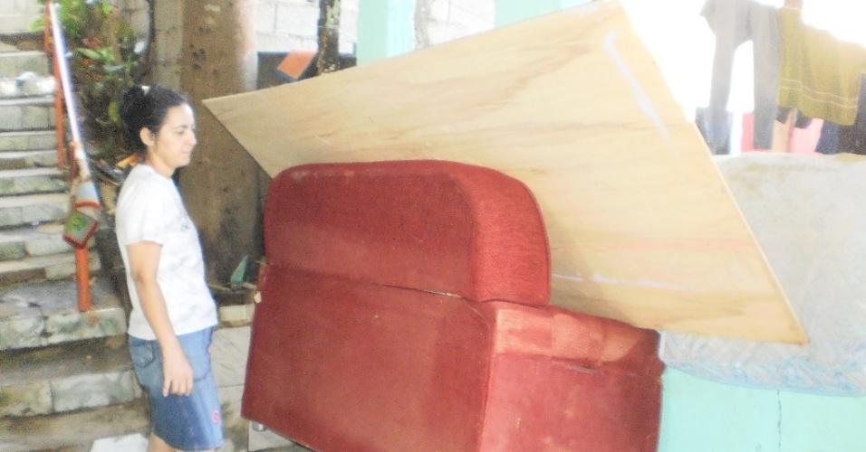 28.fev.2013 - A vendedora ambulante Irismar de Souza Alves, moradora do bairro Pilões, mostra objetos atingidos pela água em sua casa após o temporal que atingiu Cubatão (SP) entre a sexta-feira (22) e o sábado (23)