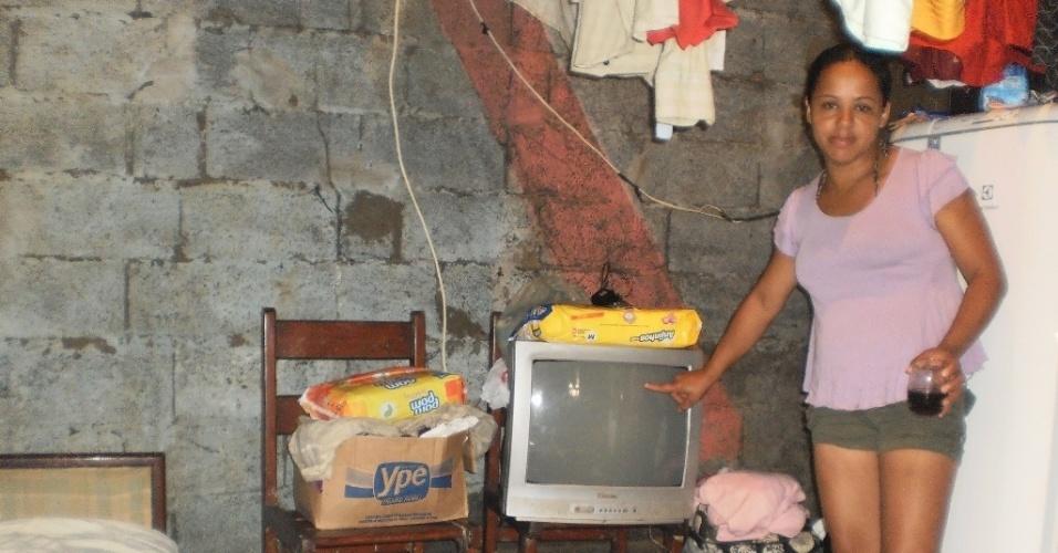 28.fev.2013 - Andreia Michelle de Souza Borba mostra televisor inutilizado pela água da chuva, que atingiu mais de dois metros de altura em sua casa, em Cubatão (SP), após o temporal que atingiu a cidade paulista entre a sexta-feira (22) e o sábado (23)