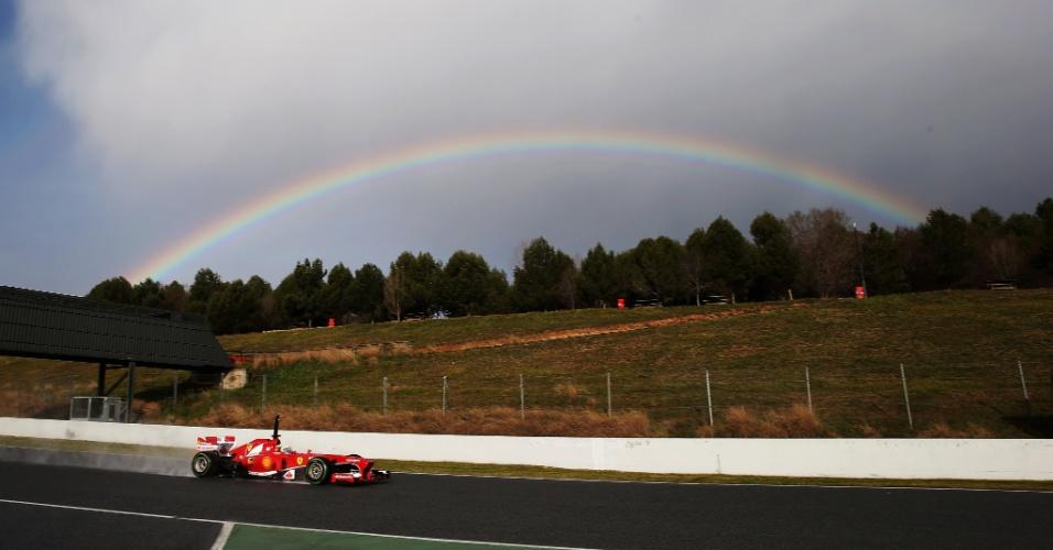28.fev.2013 - Com um arco-íris ao fundo, Felipe Massa acelera sua Ferrari pelo circuito de Barcelona durante testes coletivos