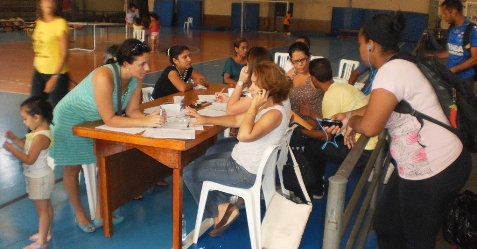 28.fev.2013 - No Ginásio Poliesportivo Castelo Branco, o Castelão, assistentes sociais cadastram famílias prejudicadas pelo temporal em Cubatão (SP)