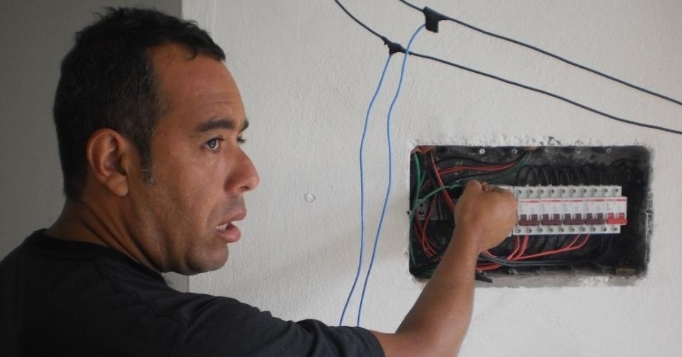 28.fev.2013 - O operador de máquinas Wagner Florêncio da Silva mostra ligação elétrica feita improvisadamente em uma casa invadida no último fim de semana, após o temporal que deixou diversas famílias desabrigadas em Cubatão (SP)