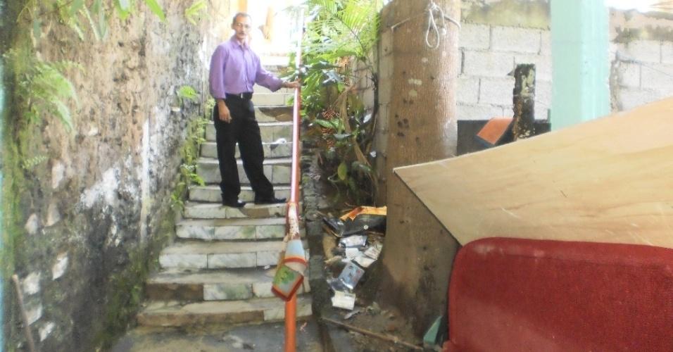 28.fev.2013 - O soldador Jones Alves da Silva aponta até onde chegou o nível da água durante o temporal registrado entre a sexta-feira (22) e o sábado (23) últimos, no bairro de Pilões, em Cubatão (SP)