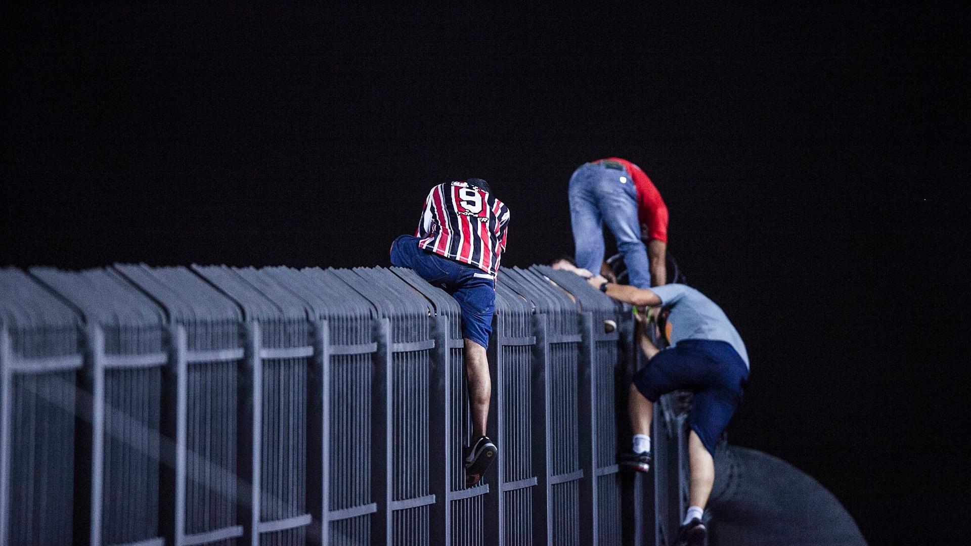 28.fev.2013 - Torcedores do São Paulo pulam grade do Morumbi para mudar de setor antes do jogo contra o The Strongest (BOL), pela Libertadores