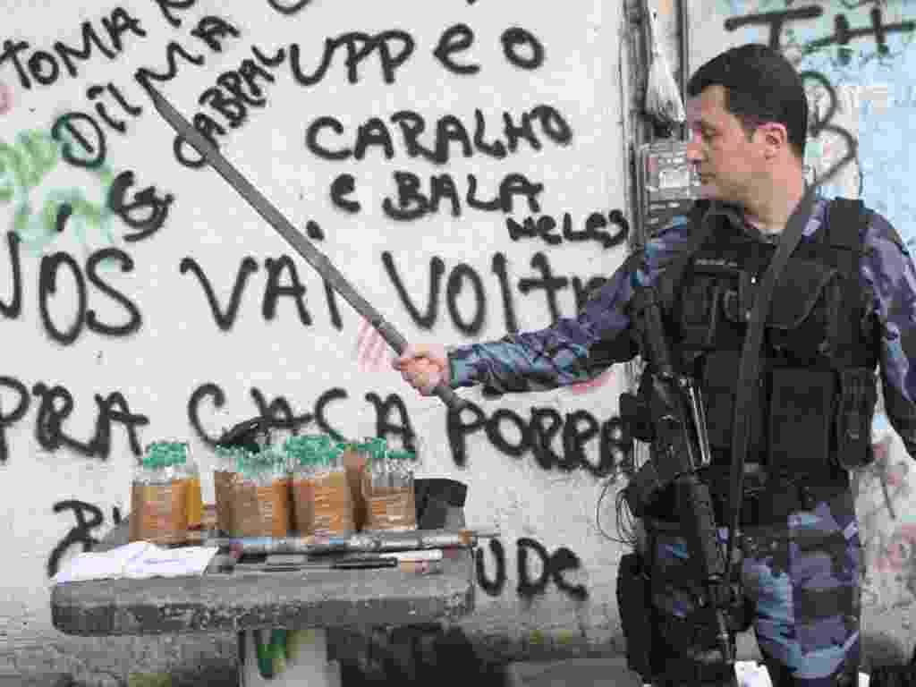 03.mar.2013 - Policial mostra espécie de espada apreendida durante ocupação de favelas no Rio de Janeiro - Zulmair Rocha/UOL