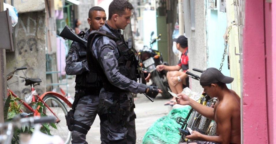 3.mar.2013 - Policiais abordam morador durante ocupação das comunidades do Complexo do Caju e da Barreira do Vasco, no Rio de Janeiro