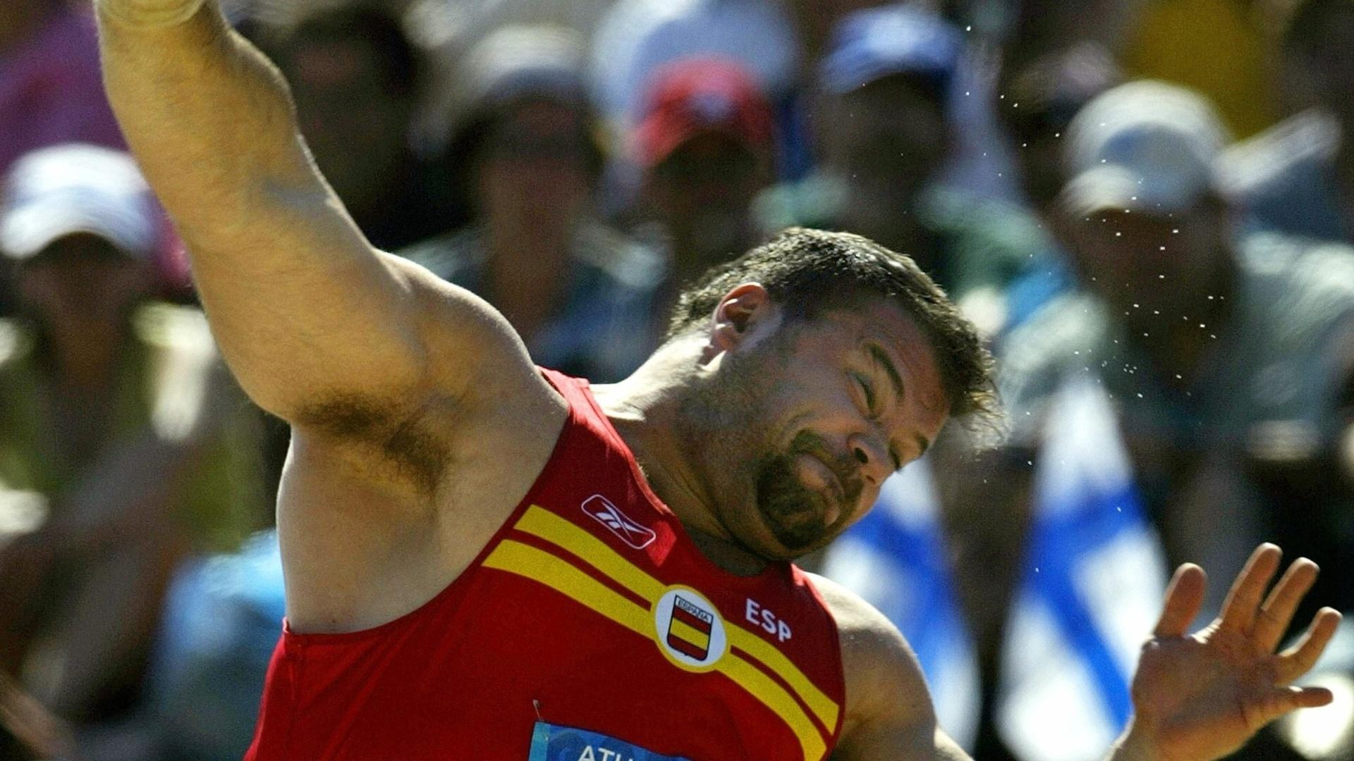 18.ago.2004 - Espanhol Manuel Martínez participa de prova de arremesso de peso durante os Jogos Olímpicos de Atenas-2004, na Grécia